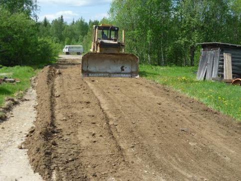 4. Трактор продолжает разравнивать дорогу.